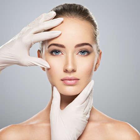 Vérification de la peau du visage avant la chirurgie plastique. Esthéticienne, toucher le visage de la femme.