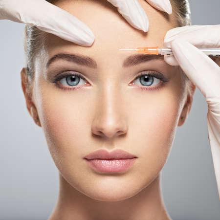 Portrait de jeune femme de race blanche obtenir injection de botox cosmétique sur le front. Belle femme obtient injection de botox dans son visage.