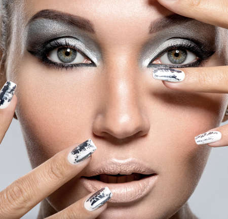 Beautiful girl with the silver makeup and  metal nails. Fashion woman portrait. LANG_EVOIMAGES
