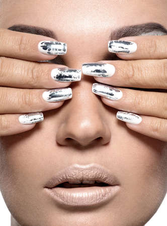 Beautiful girl with the silver metal nails. Closeup shot.