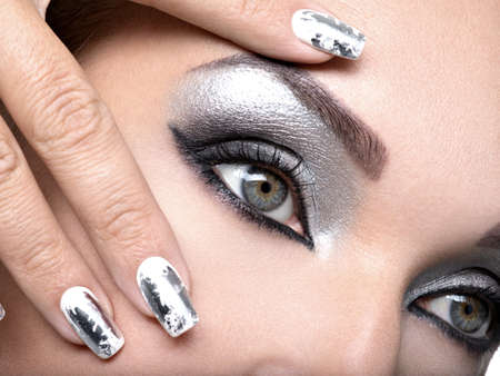 Beautiful girl with the silver  makeup of eyes and  metal nails. Fashion woman portrait. Closeup shot of female eye.
