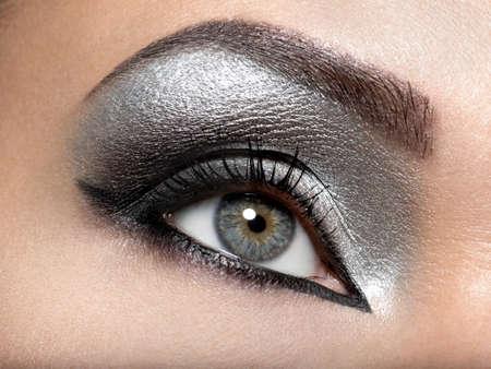 Beautiful girl with the silver  makeup of eyes. Fashion woman portrait. Closeup shot of female eye.