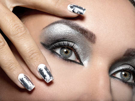 Belle fille avec le maquillage d'argent des yeux et des ongles en métal. Portrait de femme Fashion. Closeup shot d'un ?il féminin.