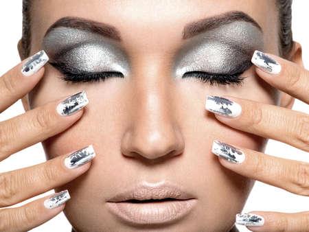 Belle fille avec le maquillage d'argent et des clous en métal. Portrait de femme Fashion.