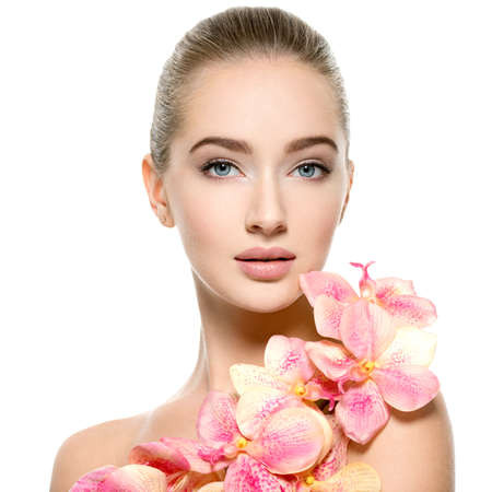 Beautiful young woman with flower in hand near at face.  Closeup portrait of caucasian girl with healthy clean skin. Skin care. beauty treatmant  - isolated on white background