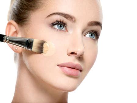 Girl applies  tonal foundation on face use makeup brush. Woman makes makeup.
