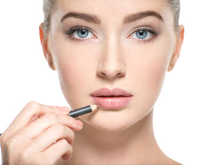 Woman apply lipstick with cosmetic pencil on the lips - isolated on white 스톡 콘텐츠