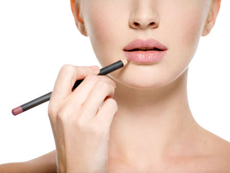 Girl apply lipstick with cosmetic pencil on the lips - isolated on white Stock Photo