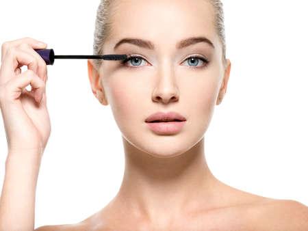 Girl makes makeup. Beautiful woman apply mascara on eyelashes  with cosmetic brush - isolated on white