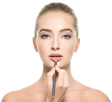 Woman apply lipstick with cosmetic pencil on the lips - isolated on white Stock Photo
