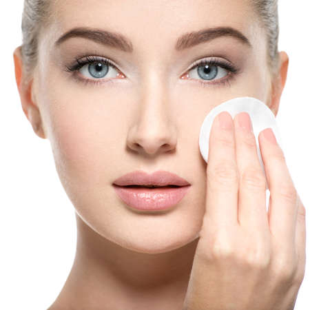 Girl removes makeup with cotton ball from face. Young woman cleans skin from cosmetic by cotton swab. Skin care concept. Stock Photo