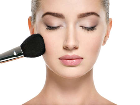 Young girl  with makeup brush near at face. White woman makes makeup - isolated