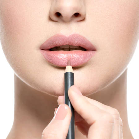 Girl apply lipstick with cosmetic pencil on the lips - isolated on white