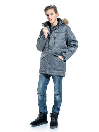 Teenage boy in winter clothes - posing over white background. Young guy in gray warm jacket and boots Banque d'images
