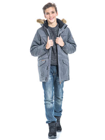 Teenage boy in winter clothes - posing over white background. Young guy in gray warm jacket and boots Stock Photo