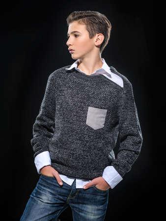 Photo of teenage handsome guy posing at studio. Fashion portrait of cute pretty teen boy