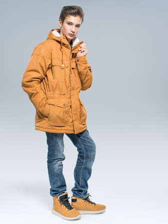 Teenage boy in winter clothes - posing over white background. Young guy in orange warm jacket and boots