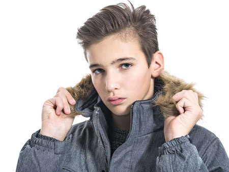 Teenage boy in winter clothes - posing over white background. Young guy in gray warm jacket and boots. Closeup portrait of handsome teen kid.
