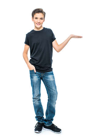 Photo of teenage young  boy holds something on palm looking at camera. Full portrait