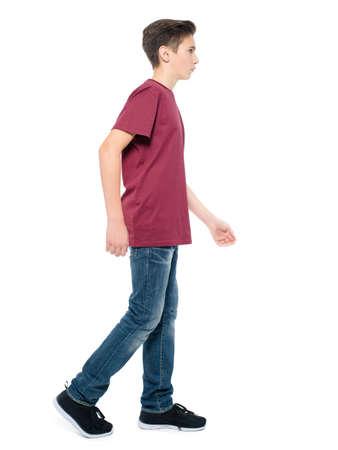 Photo of teen boy walking at studio over white background. Profile portrait