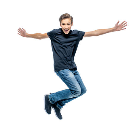 Photo of happy teenage boy jumping with hands up looking at camera. Banque d'images