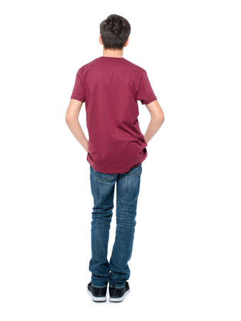 Rear view, teen boy standing at studio over white background Stock Photo