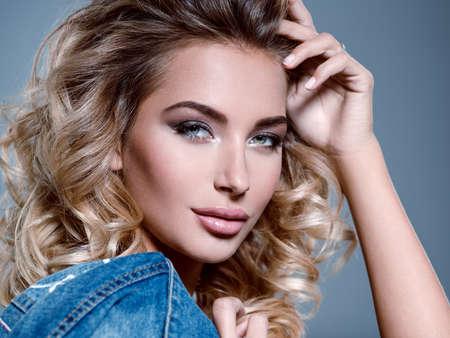 Foto von einem schönen jungen blonden Mädchen mit lockigem Haar . Close-up sinnliche sinnliche Gesicht der weißen Frau mit langen Haaren . Smokey Eye Make-up