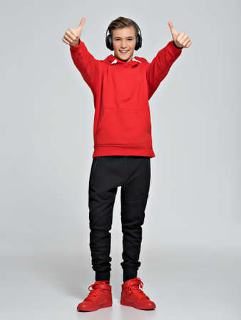 Teenage boy dressed in a red hoodie and street sneakers. Teenager wears fashionable fall clothes and shows thumbs up - posing over white background. Full portrait. Stock Photo