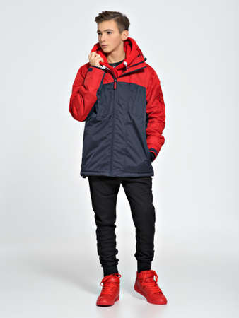 Teenage boy dressed in a sport wear. Teenager wears fashionable fall clothes - posing over white background. Full portrait.
