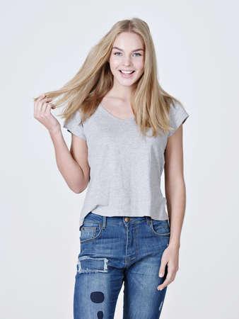 Schöne junge lächelnde kaukasische Frau mit dem langen blonden Haar , das auf weißem Hintergrund aufwirft Standard-Bild