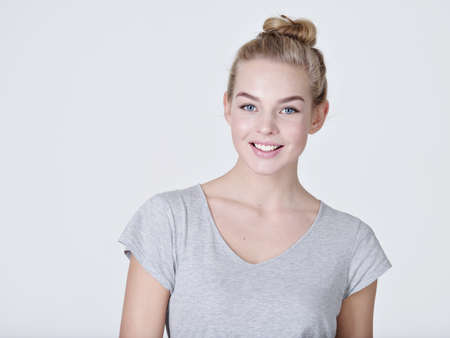Portrait of a  beautiful young smiling  girl.  Female face with toothy smile. Attractive blond girl poses at studio in a casual grey t shirt