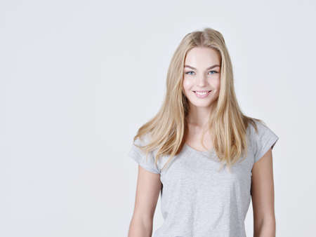 Portrait of a caucasion beautiful young smiling  girl.  Female  with toothy smile. Attractive blond girl poses at studio in a casual t shirt