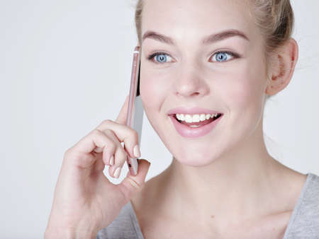 Close up portrait of a happy woman talking on the mobile phone on gray background