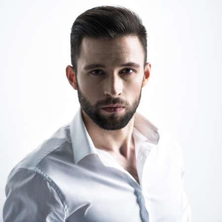 Hombre guapo con camisa blanca, posando en el estudio. Chico atractivo con peinado de moda. Hombre confiado con barba corta. Niño adulto con cabello castaño. Retrato de primer plano.