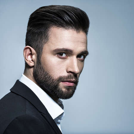 Handsome man in black suit with white shirt  - posing  at studio. Attractive guy with fashion hairstyle.  Confident man with short beard. Adult boy with brown hair. Stock fotó