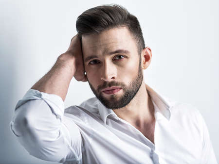 Handsome man in white shirt, posing  at studio. Attractive guy with fashion hairstyle.  Confident man with short beard. Adult boy with brown hair. Closeup portrait.