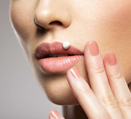 Cosmetic moisturize cream  on female lip.  Skin care  concept. Beauty treatment concept. Reklamní fotografie