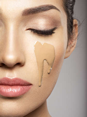 Liquid cosmetic makeup foundation is on the female face.  Beauty treatment concept. Girl makes makeup. Фото со стока