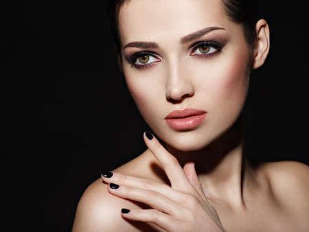 Gesicht eines schönen Mädchens mit Mode-Make-up und schwarzen Nägeln, die im Studio über dunklem Hintergrund aufwerfen Standard-Bild