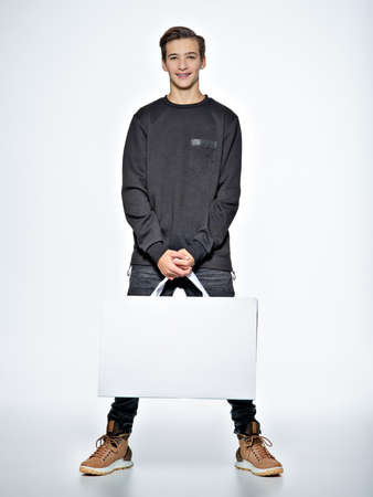 Teen boy with shopping bags. Teenage boy dressed in black trendy clothes posing at studio. Full portrait of handsome teen boy over white background.