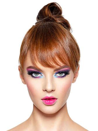 Fronte del primo piano di una bella donna con trucco vivido brillante. Modello di moda con trucco creativo dell'occhio dell'acconciatura - isolato su bianco. Ragazza con i capelli rossi. Acconciatura corta con frangia
