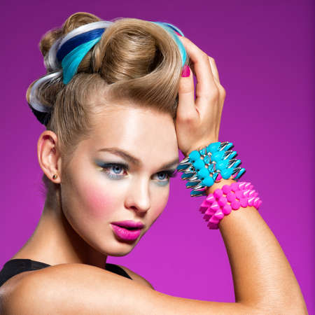 Fashion portrait of young caucasian model with bright makeup. Beautiful woman with creative hairstyle. woman with  Fashion make-up. Closeup portrait. Gorgeous face of an attractive girl - pink background. Portrait of a girl with bracelets on her hands in the form of thorns. Jewelry Imagens