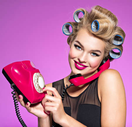 Young girl dials a phone number on an old phone. Young happy woman with blue curlers calling by retro phone.  Portrain of an atractive female using a vintage phone. 스톡 콘텐츠