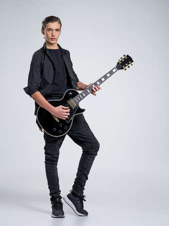 Fifteen years old guitarist with a  black electric guitar. Teenage musician holds guitar, posing at studio. The young caucasian guy with a guitar. Boys playing rock music. Heavy metal player.