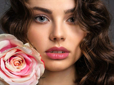 Beautiful face of a young woman with a smoky eye makeup  and rose flower. Sexy and gorgeous brown-haired woman with long curly hair. Portrait of an attractive female posing at studio. Art. Fashion mod 写真素材