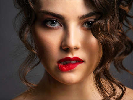 Closeup Face of a beautiful woman with a smoky eye makeup and red lipstick. Sexy brunette girl  with long curly hair. Portrait of an attractive female -  at studio. Fashion model. Beautiful eyes. Bite 写真素材