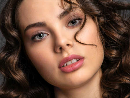 Portrait of a  beautiful woman with a smoky eye makeup. Sexy and gorgeous brunette woman with  curly hair. Portrait of an attractive female posing at studio. Fashion model