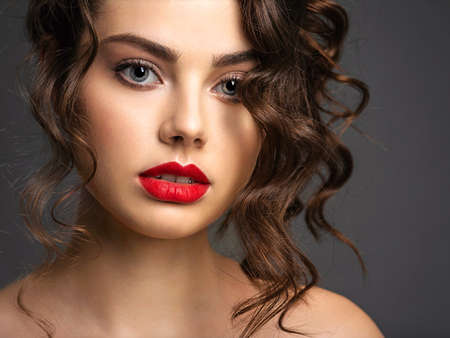Closeup Face of a beautiful woman with a smoky eye makeup and red lipstick. Sexy and gorgeous brunette girl  with long curly hair. Portrait of an attractive female -  at studio. Fashion model.