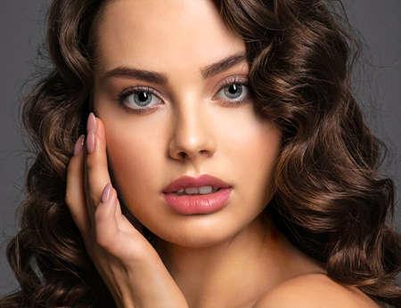 Nahaufnahmegesicht einer schönen Frau mit einem rauchigen Augenmake-up. Sexy und wunderschöne braunhaarige Frau mit langen lockigen Haaren. Porträt einer attraktiven Frau, die im Studio aufwirft.