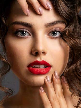 Nahaufnahme Gesicht einer schönen Frau mit einem rauchigen Augenmake-up und rotem Lippenstift. Sexy Brunettemädchen mit dem langen gelockten Haar. Porträt einer attraktiven Frau - im Studio. Mode-Modell. Wunderschöne Augen.